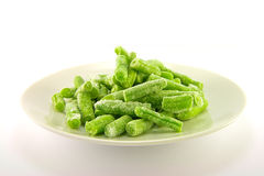 Frozen French Beans. Pile of frozen french beans on a white plate with plain background Stock Images