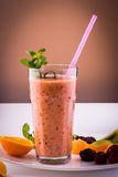 Frozen and fresh fruits smoothie with mint. Glass of smoothie made of frozen blackberries, oranges, yogurt and strawberries royalty free stock photos