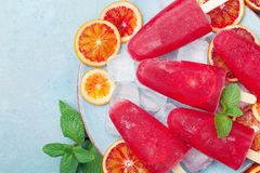 Frozen fruit juice. Homemade citrus ice cream or popsicles decorated mint leaves and orange slices on blue table top view. Summer food Stock Photography