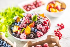 Frozen fruits blueberries blackberry raspberry red currant peach and herbs melissa.  royalty free stock images