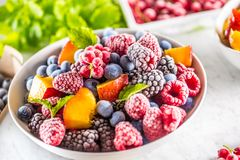 Frozen fruits blueberries blackberry raspberry red currant peach and herbs melissa.  stock image