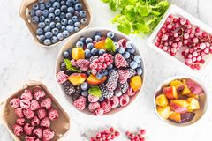 Frozen fruits blueberries blackberry raspberry red currant peach and herbs melissa.  stock photos