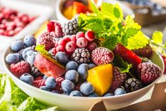 Frozen fruits blueberries blackberry raspberry red currant peach and herbs melissa.  stock images