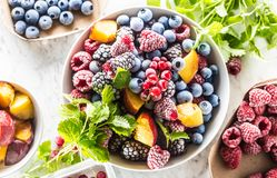 Frozen fruits blueberries blackberry raspberry red currant peach and herbs melissa.  royalty free stock photography