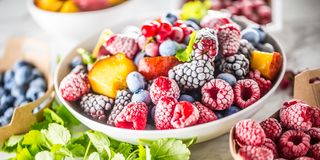 Frozen fruits blueberries blackberry raspberry red currant peach and herbs melissa.  royalty free stock photos