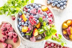 Frozen fruits blueberries blackberry raspberry red currant peach and herbs melissa.  royalty free stock image