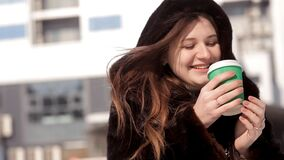Frozen girl drinking coffee in the winter on the street.  stock footage