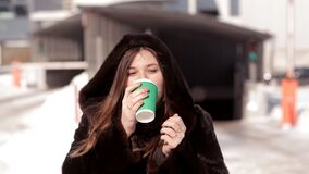 Frozen girl drinking coffee in the winter on the street.  stock video