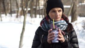 Frozen girl drinking coffee in winter on the street.  stock video