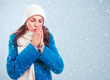 Frozen girl heats hands among winter snowstorm Royalty Free Stock Images