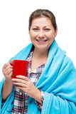 A frozen girl in a plaid with a red mug of hot tea on a white. Background Royalty Free Stock Photo