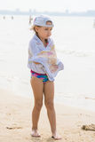 Frozen girl standing on the beach wrapped in a towel Royalty Free Stock Images