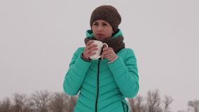 Frozen girl warms herself with hot mug in the frosty fresh air in winter. Drink tea in winter park. Hot coffee. Frozen girl warms herself with hot mug in the Stock Photo
