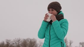 Frozen girl warms herself with hot mug in the frosty fresh air in winter. Drink tea in winter park. Hot coffee. Frozen girl warms herself with hot mug in the Stock Image
