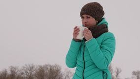 Frozen girl warms herself with hot mug in the frosty fresh air in winter. Drink tea in winter park. Hot coffee. Frozen girl warms herself with hot mug in the Royalty Free Stock Photography