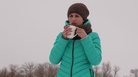 Frozen girl warms herself with hot mug in the frosty fresh air in winter. Drink tea in winter park. Hot coffee. Frozen girl warms herself with hot mug in the Stock Photos