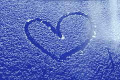 Frozen glass of a car on a winter day, drawing heart.  stock photos