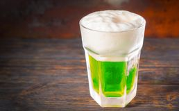 Frozen glass with a green beer and a large head of foam on old d. Ark desk. Drink and beverages concept Stock Image