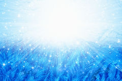 Frozen glass. Winter background - blue icy frozen window glass with bright sunlight and stars Stock Image