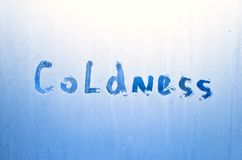 On a frozen glass it is written coldness. Inscription on the frozen glass stock photos