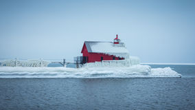Frozen Grand Haven Lighthouse jutting out into the water. Lake Michigan Light covered in ice Stock Photo