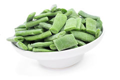 Frozen green beans. A bowl with frozen chopped green beans on a white background Royalty Free Stock Photography