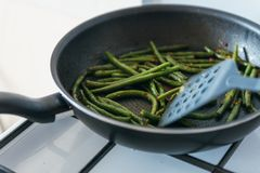 Frozen green beans in frying pan, salt, pepper and vegetable oil stock image