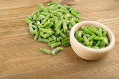 Frozen Green Beans. Heap of Chopped Frozen Green Beans on Wood Background royalty free stock photo