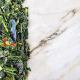 Frozen. Green leafy vegetables on a marble surface Royalty Free Stock Photo