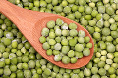 Frozen green peas in a wooden spoon Royalty Free Stock Photography