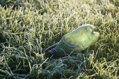 A frozen green plastic garbage bottle contributing to environmental pollution in a field of frosty grass in wintertime stock image