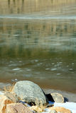 Frozen green river and rocks Royalty Free Stock Image