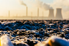 Frozen ground at oil refinery. Close up of frozen ground with steam from smokestacks from oil refinery at dusk stock image
