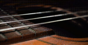 Frozen Guitar. A close-up photo of a guitar with ice particles and frozen metal strings stock photo