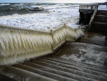 Frozen handrails on the coast increased humidity. The waves on the coast after the storm, huge icicles have on the railing of the embankment there`s no bearing stock image