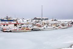 The frozen harbor of the Icelandic fishing village of Höfn in winter, with its boats laid up until the thaw royalty free stock image