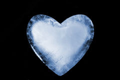 Frozen Heart. An ice cold blue heart. Over black royalty free stock photo
