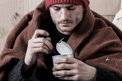 Frozen homeless man eat. Food from cans Stock Photos