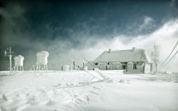 Frozen hut meteo station. Frozen cottage in the high mountains, covered with ice Royalty Free Stock Photography