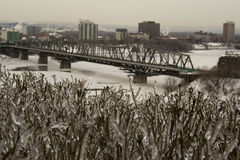 Frozen ice cityscape winter capital city ottawa. Frozen ice cityscape winter capital city canada ottawa bridge river buildings in background cold temperature royalty free stock images
