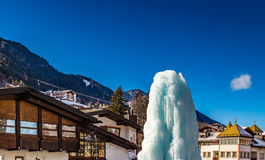 Frozen ice fountain in snowy alpine village. In Italy illuminated by sun with mountains in the background Stock Photo