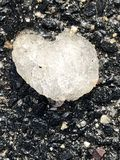 Frozen ice heart black asphalt background royalty free stock photo