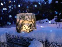 Frozen ice lantern with spruce twigs. In snow, lit with candle light royalty free stock photos
