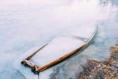 Frozen into ice of river, lake, pond old wooden boat. Forsaken r Stock Image