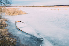 Frozen into ice of river, lake, pond old wooden boat. Forsaken r Royalty Free Stock Image