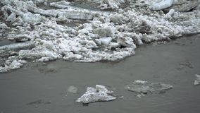 Frozen ice river is melting in spring with ice flakes flowing. Cracked ice floating on the river in spring time. Global. Warming stock video footage