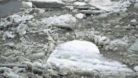 Frozen ice river is melting in spring with ice flakes flowing. Cracked ice floating on the river in spring time. Global. Warming stock footage