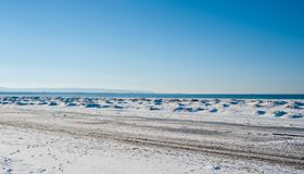 Frozen ice and sand dunes on beach in winter. Frozen ice and sand dunes on beach in winter by lake under clear blue sky, near Georgian Bay, Ontario, Canada Stock Images