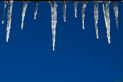 Frozen Icicles on Blue Sky Background Royalty Free Stock Photos