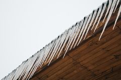 Frozen icicles on the roof of the wooden house, top floor wooden mansion. Icy weather winter scene. Frozen icicles on the wooden roof, top floor wooden mansion royalty free stock images